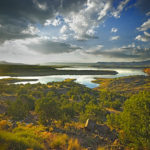 this is a view of Lake Abiquiu at sunset with clouds and lush forest surrounds